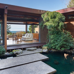 Design ideas for a large asian partial sun backyard concrete paver landscaping in Other for spring.