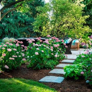 Idée de décoration pour un grand jardin arrière tradition l'été avec une exposition partiellement ombragée, des pavés en brique et un massif de fleurs.