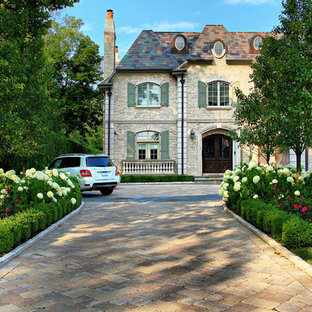 Traditional front yard driveway in Chicago with concrete pavers and with flowerbed.