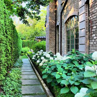 Cette image montre un jardin arrière traditionnel avec une entrée ou une allée de jardin et des pavés en pierre naturelle.