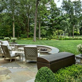 Großer Klassischer Garten im Sommer, hinter dem Haus mit Kamin, direkter Sonneneinstrahlung und Natursteinplatten in Chicago
