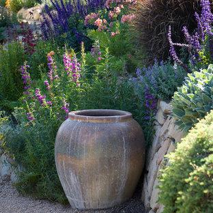 На фото: большой участок и сад на переднем дворе в средиземноморском стиле с подпорной стенкой и покрытием из гравия