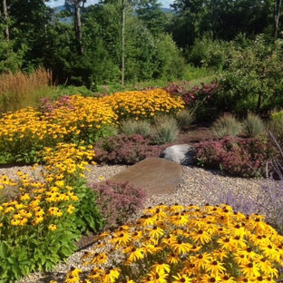 This is an example of a large traditional full sun backyard gravel landscaping in Boston.