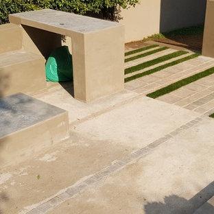 Mittelgroßer Stilmix Garten neben dem Haus mit Kamin, direkter Sonneneinstrahlung und Betonplatten in Sonstige