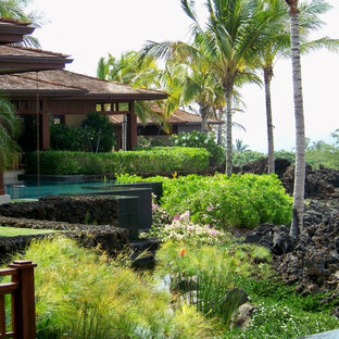 This is an example of a mid-sized tropical full sun backyard stone retaining wall landscape in Hawaii.