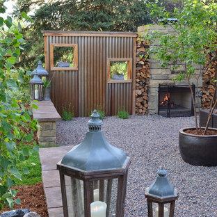 Kleiner Moderner Kiesgarten hinter dem Haus mit direkter Sonneneinstrahlung und Kamin in Sonstige