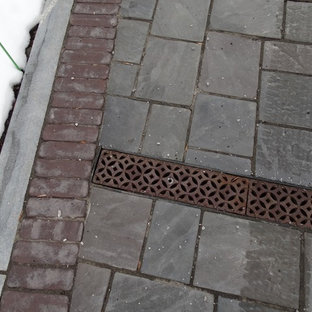 Photo of a traditional front yard concrete paver landscaping in New York for winter.