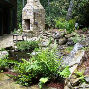 Inspiration for a traditional partial sun backyard stone landscaping in Other with a fireplace for summer.