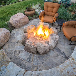Inspiration for a large traditional partial sun backyard stone landscaping in Denver with a fire pit for summer.