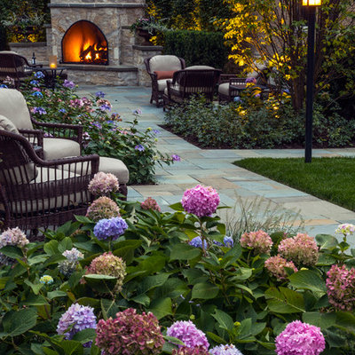 Design ideas for a large traditional partial sun backyard stone formal garden in Chicago with a fireplace.