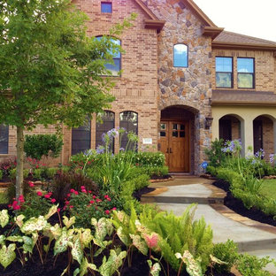 Inspiration for a large traditional full sun front yard stone landscaping in Houston for spring.