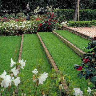 Réalisation d'un grand jardin arrière tradition avec des pavés en brique et des bordures.