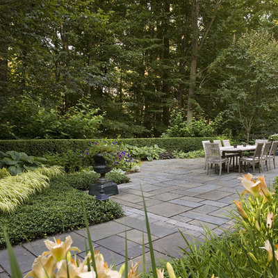 Photo of a traditional shade backyard stone landscaping in New York.