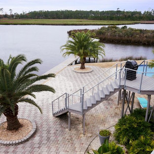 Inspiration for a coastal full sun backyard stone landscaping in New Orleans.