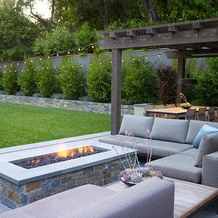 Inspiration pour un grand jardin à la française avant minimaliste avec un foyer extérieur, une exposition ensoleillée et des pavés en pierre naturelle.