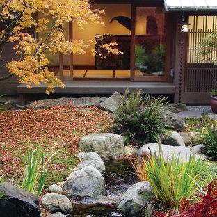 Inredning av en asiatisk mellanstor trädgård i full sol, med en fontän och trädäck