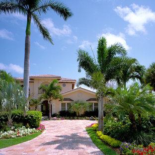 Idee per un grande vialetto d'ingresso tropicale esposto in pieno sole davanti casa in estate con pavimentazioni in pietra naturale