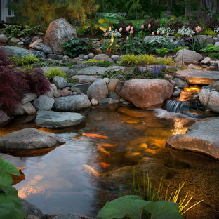 This is an example of a mid-sized modern courtyard stone water fountain landscape in Detroit.