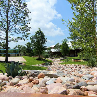 Inspiration for a huge rustic drought-tolerant side yard gravel retaining wall landscape in Austin.