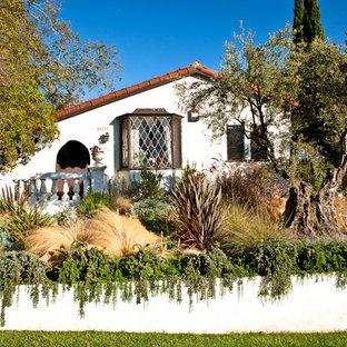 Foto di un giardino mediterraneo davanti casa con un muro di contenimento