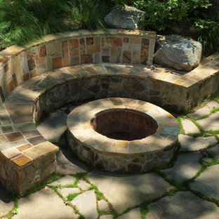 This is an example of a mid-sized contemporary partial sun backyard stone landscaping in Other with a fire pit.