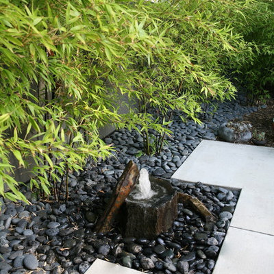 This is an example of a mid-sized asian full sun backyard stone landscaping in Orange County.