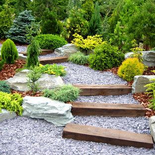 Idée de décoration pour un jardin tradition avec une pente, une colline ou un talus, une entrée ou une allée de jardin et du gravier.
