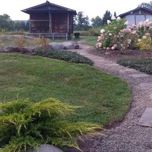 Immagine di un grande laghetto da giardino etnico esposto a mezz'ombra dietro casa con pavimentazioni in pietra naturale