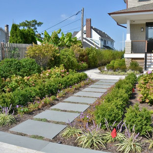 This is an example of a mid-sized contemporary full sun front yard stone landscaping in New York.