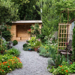 Foto de jardín de secano, tradicional, de tamaño medio, en patio trasero, con gravilla y exposición parcial al sol