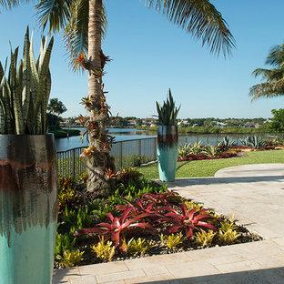 Idee per un grande giardino tropicale esposto in pieno sole dietro casa con un giardino in vaso e pavimentazioni in pietra naturale