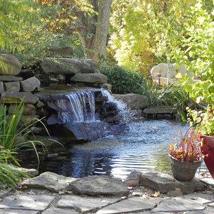 Неиссякаемый источник вдохновения для домашнего уюта: большой геометрический сад на заднем дворе в классическом стиле с прудом, полуденной тенью и дорожками из брусчатки из камня