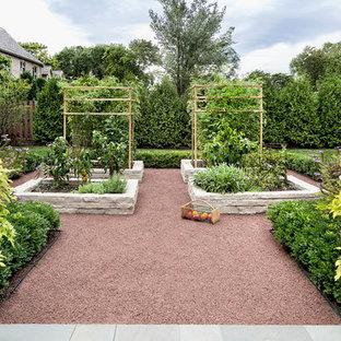 Klassisk inredning av en trädgård i full sol, med en köksträdgård och grus