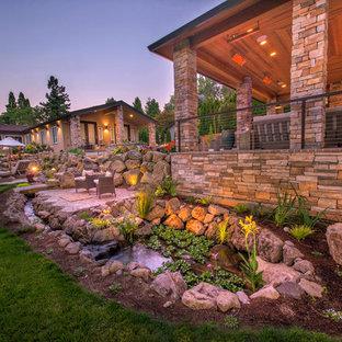 Aménagement d'un grand jardin avant craftsman au printemps avec une exposition partiellement ombragée et des pavés en béton.