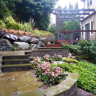Design ideas for a mid-sized transitional shade backyard stone retaining wall landscape in Seattle.