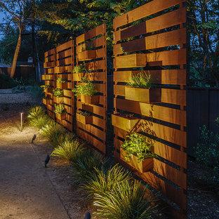 Ispirazione per un grande giardino moderno esposto a mezz'ombra dietro casa con uno spazio giochi