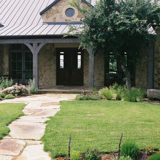 Inspiration for a large rustic full sun front yard stone landscaping in Austin for summer.