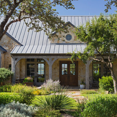 This is an example of a large rustic drought-tolerant and full sun front yard stone landscaping in Austin for summer.