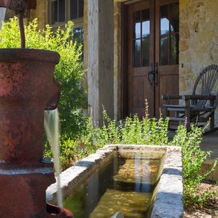 This is an example of a large rustic full sun front yard gravel water fountain landscape in Austin.