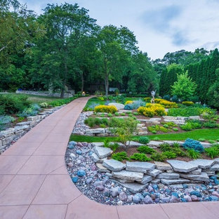 This is an example of a large traditional full sun front yard gravel landscaping in Milwaukee.