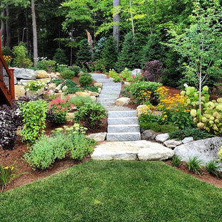 This is an example of a mid-sized rustic full sun backyard stone landscaping in Manchester for summer.