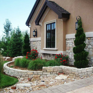 This is an example of a large traditional partial sun front yard brick landscaping in Denver.