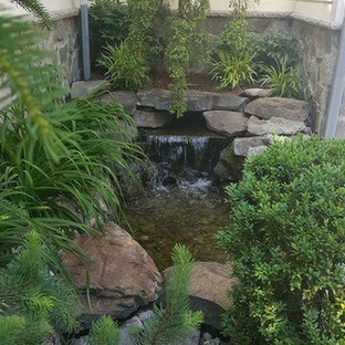 Photo of a small traditional backyard brick waterfall in New York.