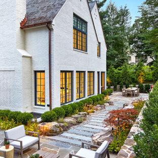 Aménagement d'un grand jardin arrière contemporain l'été avec un chemin, une exposition ensoleillée et des pavés en pierre naturelle.