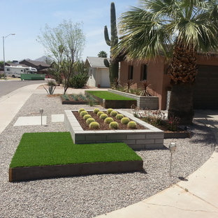 This is an example of a mid-sized contemporary drought-tolerant and full sun front yard gravel landscaping in Phoenix for summer.