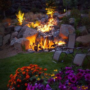 На фото: большой участок и сад на склоне в стиле кантри с местом для костра и мощением клинкерной брусчаткой
