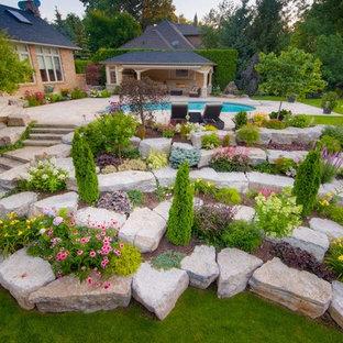 Неиссякаемый источник вдохновения для домашнего уюта: огромный солнечный, летний участок и сад на склоне в классическом стиле с хорошей освещенностью, покрытием из каменной брусчатки и камнем в ландшафтном дизайне