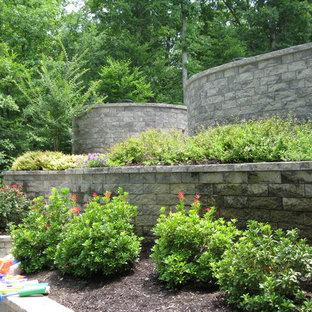 Modelo de jardín tradicional, de tamaño medio, en primavera, en patio trasero, con muro de contención, exposición parcial al sol y adoquines de piedra natural