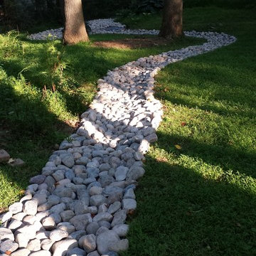Landscaping and river rock drainage swale
