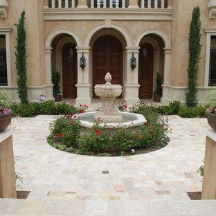 Ejemplo de jardín mediterráneo, grande, en patio trasero, con fuente, exposición parcial al sol y adoquines de piedra natural